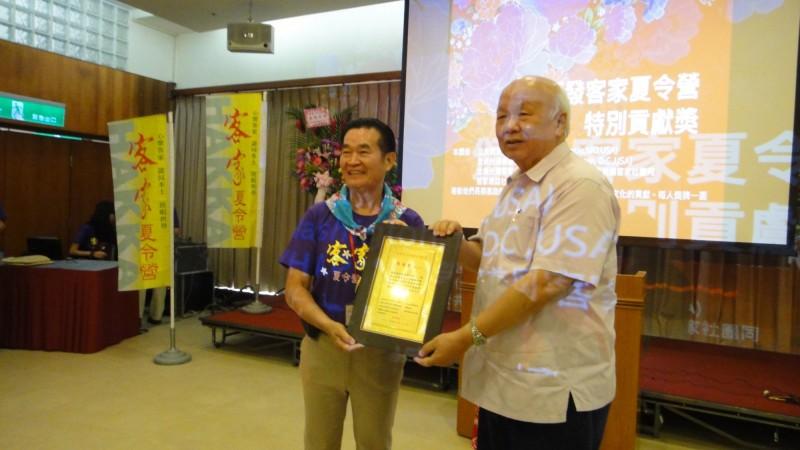 林光華(右)頒奬給客家夏令營貢獻獎得主周德君(左)。(記者李容萍翻攝)