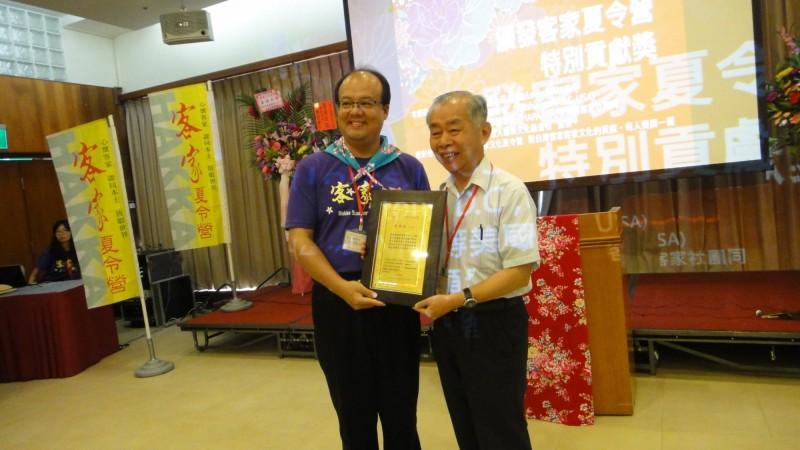 營長陳石山(右)頒奬給客家夏令營貢獻獎得主徐煥昇(左)。(記者李容萍翻攝)