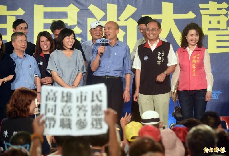 支持者舉起答應帶職參選紙張。(記者張忠義攝)