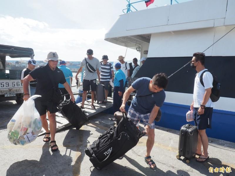 綠島遊客提前結束行程,也不忘帶回在島上製造的垃圾,響應「多背一公斤」活動。(記者王秀亭攝)
