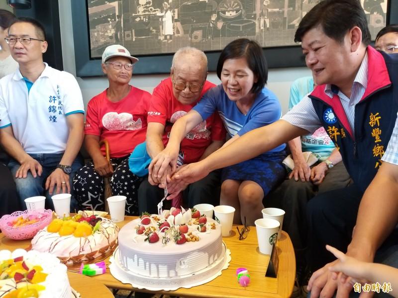 102歲鄧爺爺(中)由新豐鄉長許秋澤(右1)等人陪同切生日大蛋糕,臉上綻放幸福的笑容。 (記者廖雪茹攝)