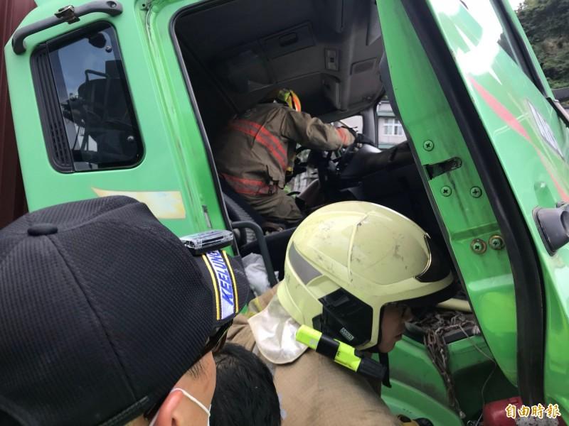 消防隊員進入車內救出受困駕駛。(記者吳昇儒攝)