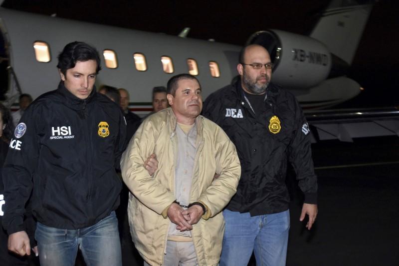 墨西哥大毒梟古茲曼(中)17日遭判處終身監禁,將在美國被關到死。圖為古茲曼在2017年被從墨西哥引渡到美國受審、搭機抵達美國時被執法人員一左一右架離。(美聯社)