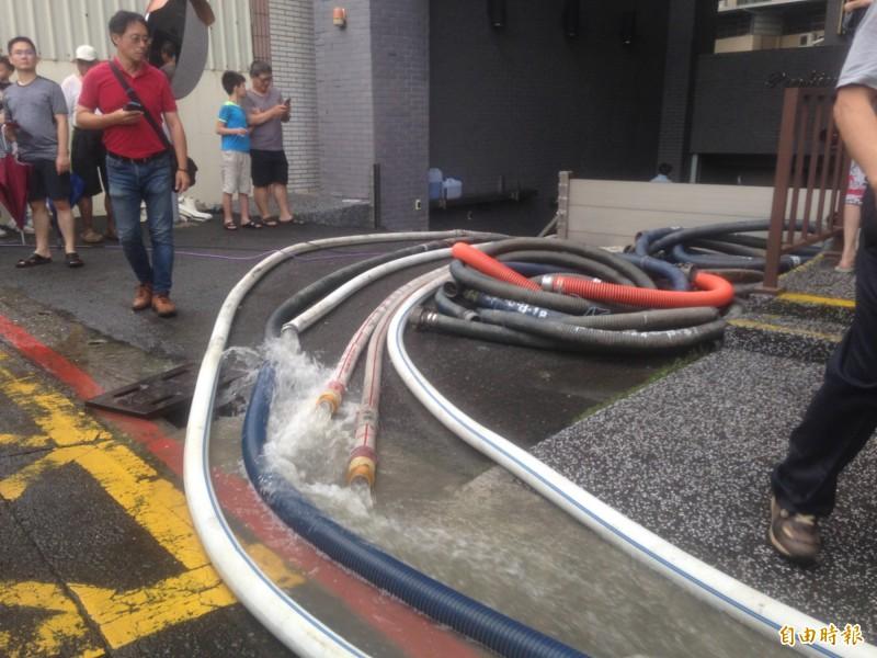 抽水機抽除積水。(記者黃旭磊攝)
