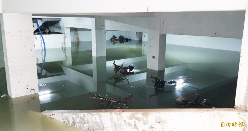 鳳山「大眾家園」公寓大廈地下室積水未退,許多車輛還泡在水裡。。(記者陳文嬋攝)