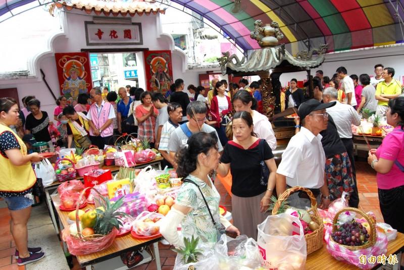 觀音媽成道紀念日在開化寺舉辦典禮,一大早就有許多信眾報到,供桌上擺滿鮮花。(記者林良哲攝)