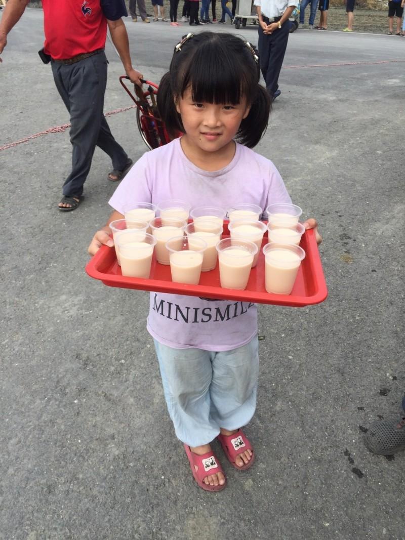 合興宮睽違70年舉行繞境,小妹妹端茶給信徒解渴。(記者陳冠備翻攝)
