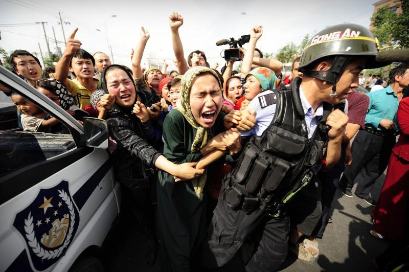圖為新疆烏魯木齊街頭參與示威的穆斯林婦女,遭到中國公安強行拘捕。(法新社檔案照)