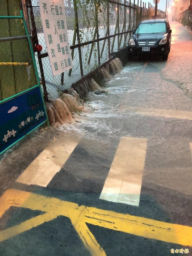 高雄七一九豪雨挾帶泥沙成為滾滾黃水,從鐵路園道流到馬路。(記者陳文嬋攝)