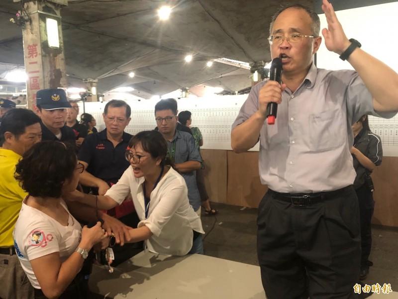王夢龍(圖前排右一)激動跪在桌上與攤商理論、說明;一旁的議員郭昭巖(左二)也趨前向汪昭華(前排左二)理論。(記者郭安家攝)