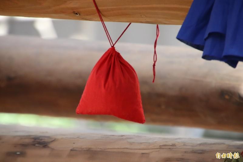 紅袋內裝著五榖種,象徵「地」,祝福五榖豐登。(記者黃美珠攝)