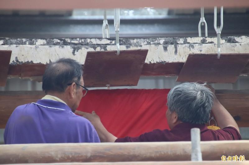 大木作匠師劉鴻林(右)今天帶領潘家後裔代表一起替梁眼纏縛上紅布,象徵祈福。(記者黃美珠攝)