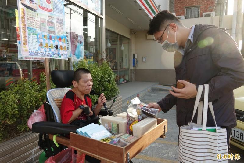 慢飛天使黃囿鈞賣自己的書、還有友善米與朋友家的產品,路過民眾自行挑選,連付費都是自己找零。(記者劉曉欣攝)