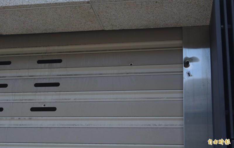 賴姓男子昨晚在太平新安街朝透天別墅開槍,鐵捲門上可看到3個明顯的彈孔。(記者陳建志攝)