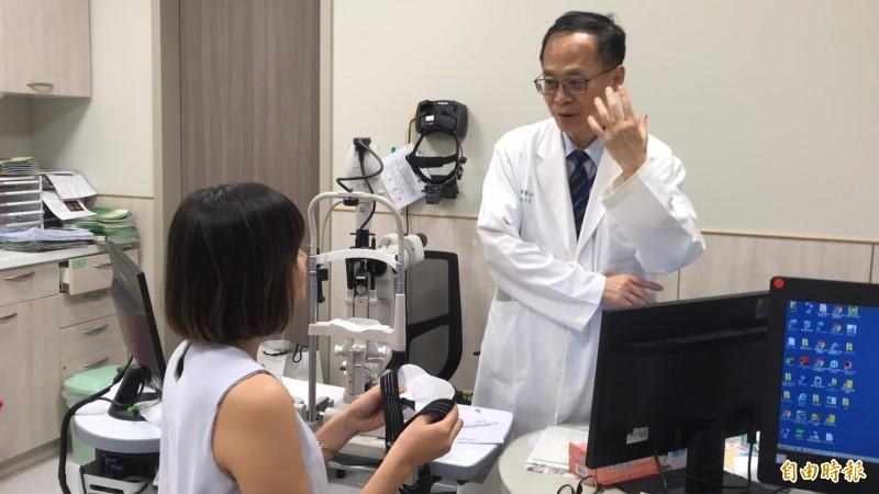 中國醫藥大學新竹附設醫院眼科主任陳瑩山(右)對病患解釋她手上恆溫式熱敷眼罩的安全可靠處。(記者黃美珠攝)