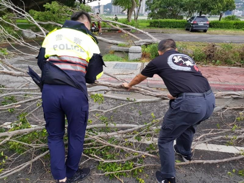 新北市八里區龍米路二段傳出路樹遭強風追倒擋路,警方、消防先將路樹推至路邊,配合大型機具排除,還道於民。(記者吳仁捷翻攝)