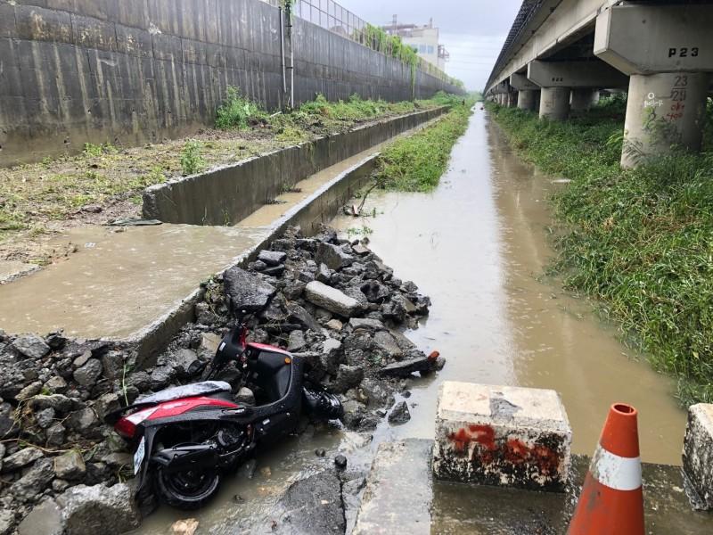 高雄市岡山區崑山西巷高速公路下方一處工地,今天上午發現一部機車摔倒在水中,但機車騎士不見人影,疑似遭大水沖走。(高市議員高閔琳提供)