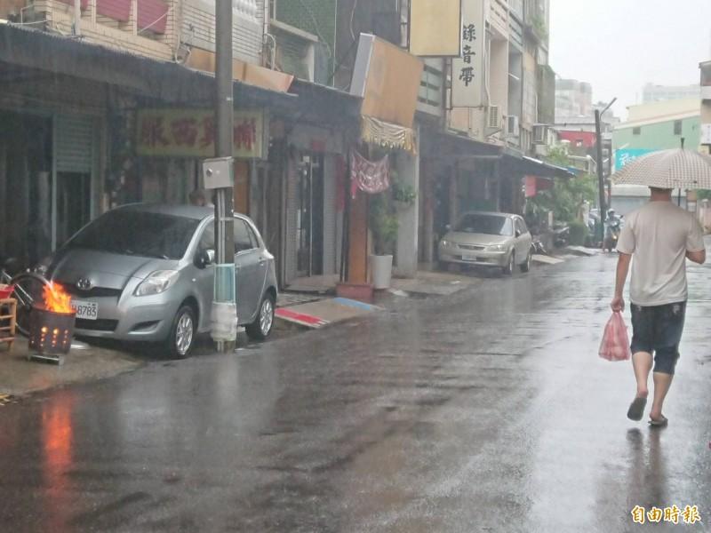 台南市今日大雷雨影響,市區部份未積淹水,民眾生活如日常,照樣中元拜拜、出門撐傘買便當。(記者洪瑞琴攝)