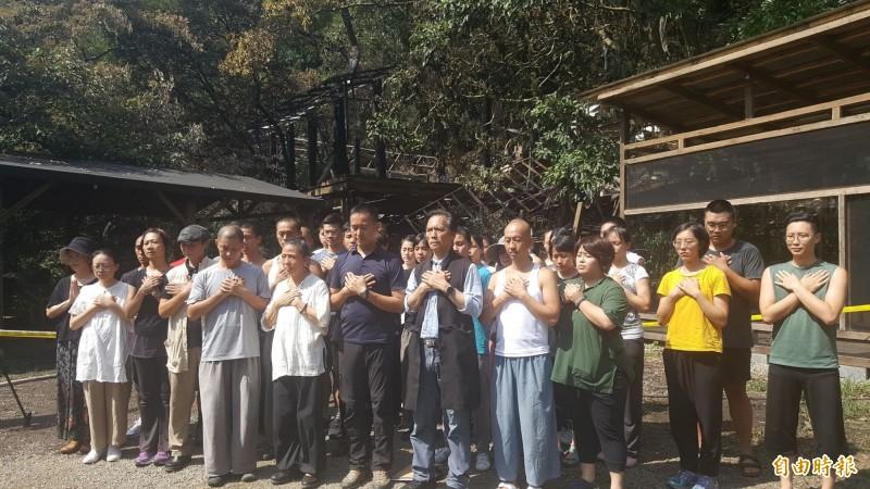 《優人神鼓》藝術總監劉若瑀今下午帶領團員,站在遭毀的建物前,雙手交叉護心祈禱。(記者楊心慧攝)