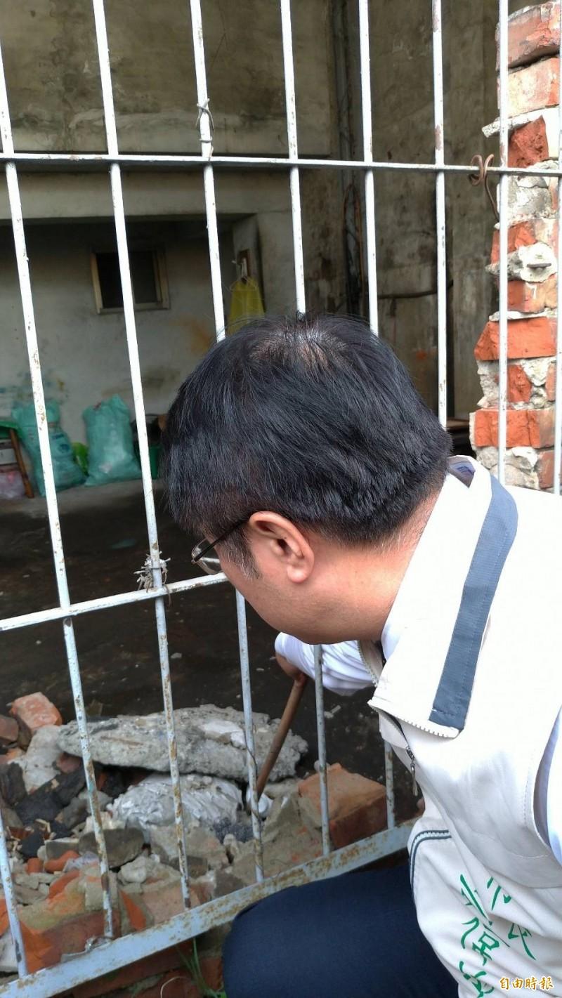 台南市長黃偉哲以棍子把南鐵待拆戶內的積水破碗打翻,避免孳生病媒蚊。(記者王俊忠攝)