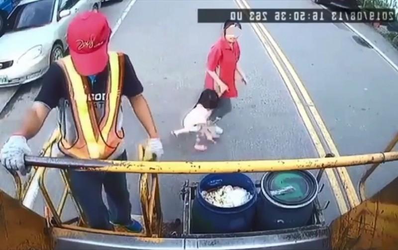 超商店員丟完垃圾,牽著女童準備過馬路。(翻攝畫面)
