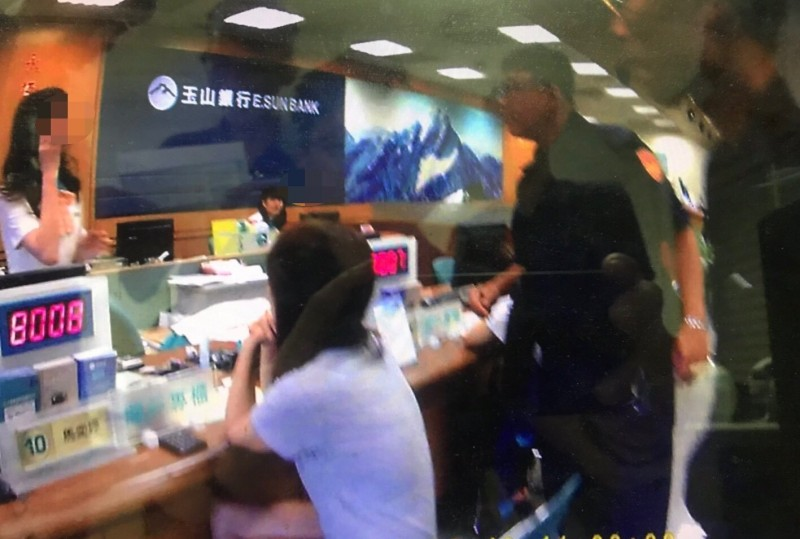 員警與行員力阻王女(左2坐著女子)遭國際愛情騙子訛詐。(記者洪臣宏翻攝)