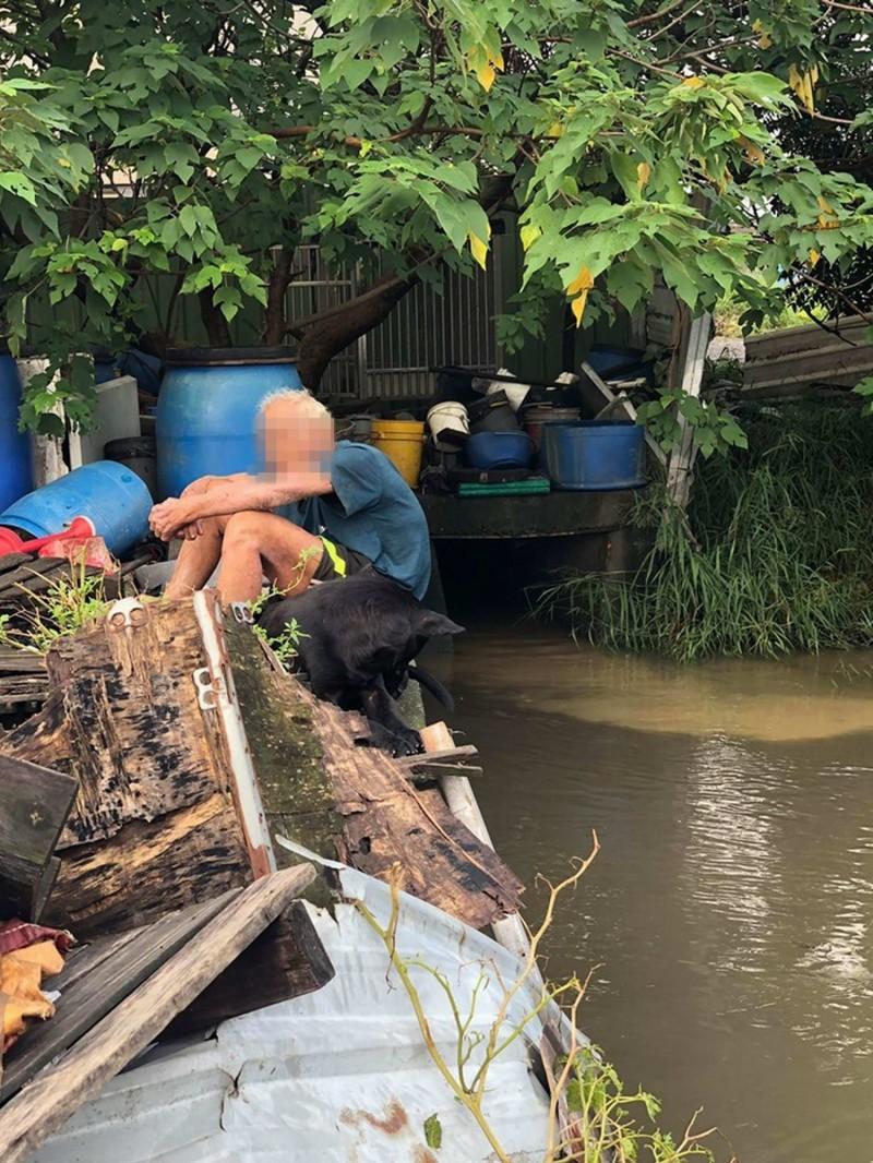 16隻流浪狗被圍捕,飼養狗群的老翁失落地坐在河邊。(記者湯世名翻攝)