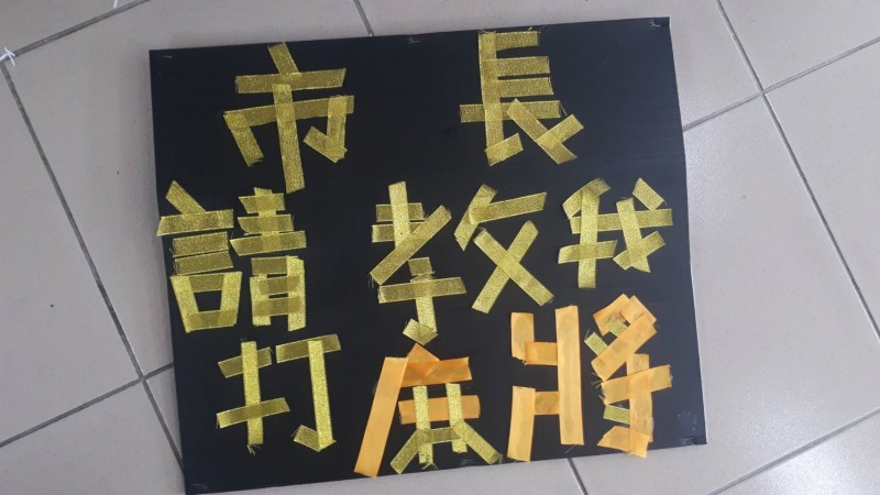 國民黨總統參選人韓國瑜今天到新竹廟宇走透透,下午在關西太和宮前,有民眾舉牌「市長請教我打麻將」、「每周任務批公文(50/225)」酸韓。 (民眾提供)
