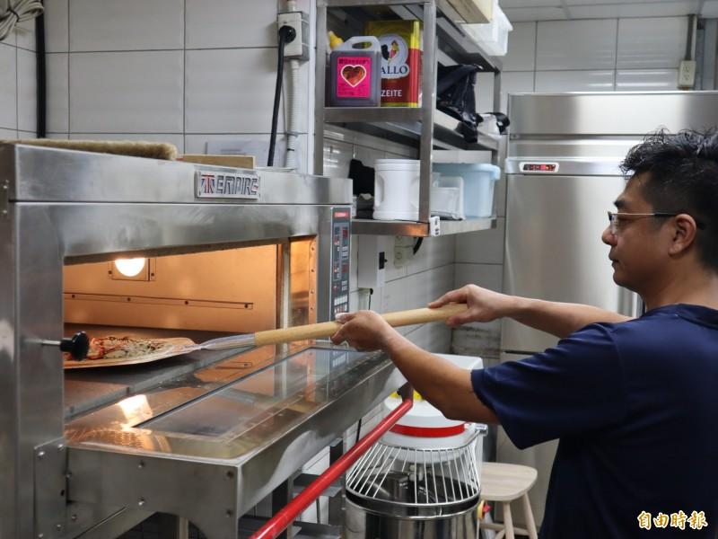樂樂義式廚房的員工正將手工薄皮披蕯放入電爐中烤熟。(記者歐素美攝)