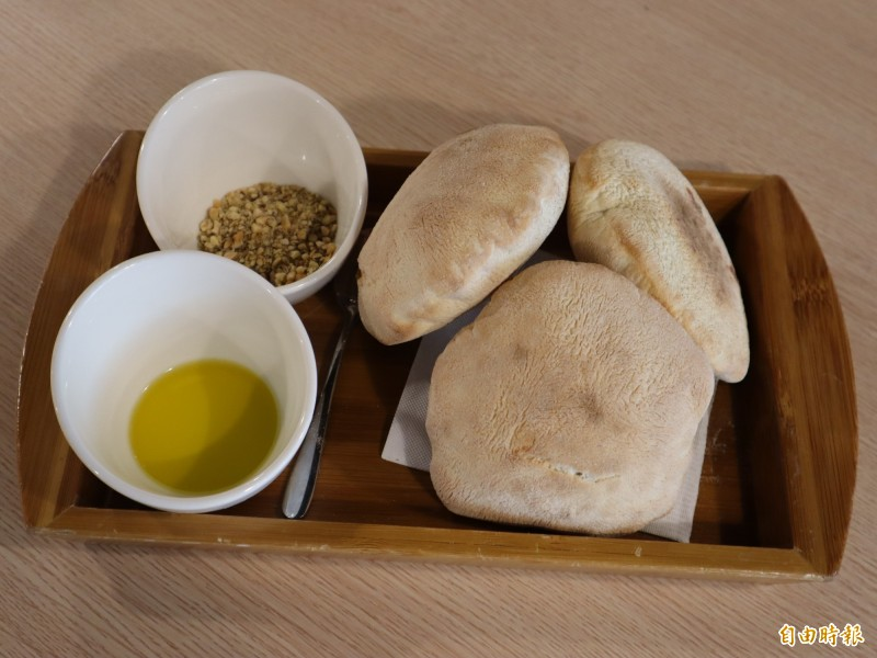 簡單的雲朵麵包,搭配夜橄欖油及杏仁粒混合香料一起食用,很特別。(記者歐素美攝)