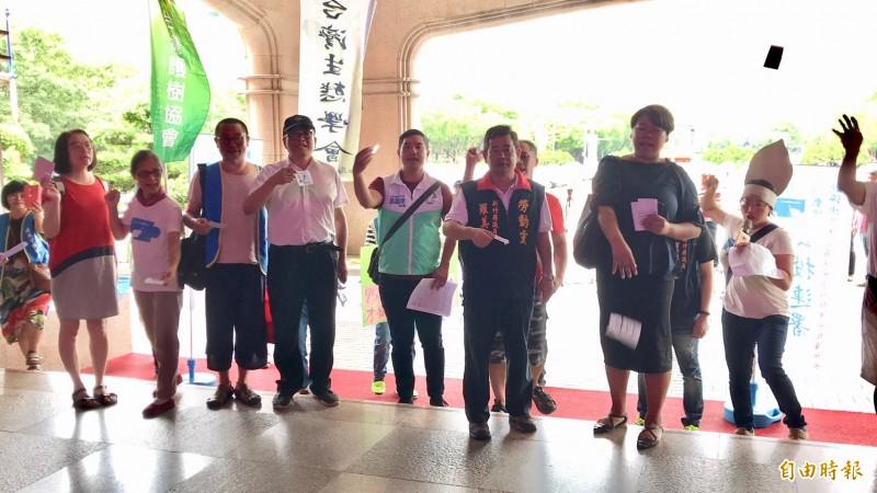 爭取喝好水的團保團體們用手中寫了重金屬名的紙片當做「雞蛋」,紛紛擲向縣府,抗議縣長楊文科神隱。(記者黃美珠攝)