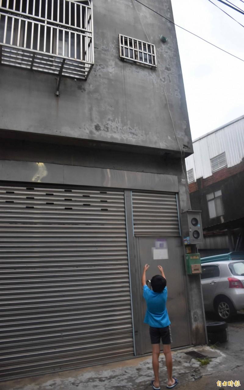 2樓一大一小的鐵窗,成了少女與外界聊天、用繩子收受物品的窗口,圖中人物與新聞無關。(記者李容萍攝)
