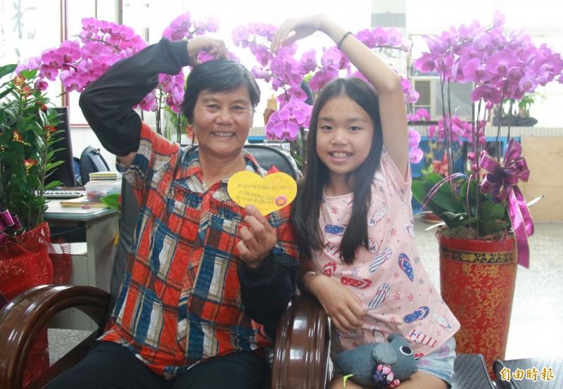 總統教育獎陳美芳(右)在祖父母節前夕,送上卡片給阿嬤洪秋霞(左),兩人開心比愛。(記者陳冠備攝)