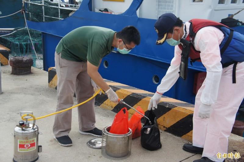 防檢人員現場為豬肉消毒,防止非州豬瘟入侵。(記者劉禹慶攝)
