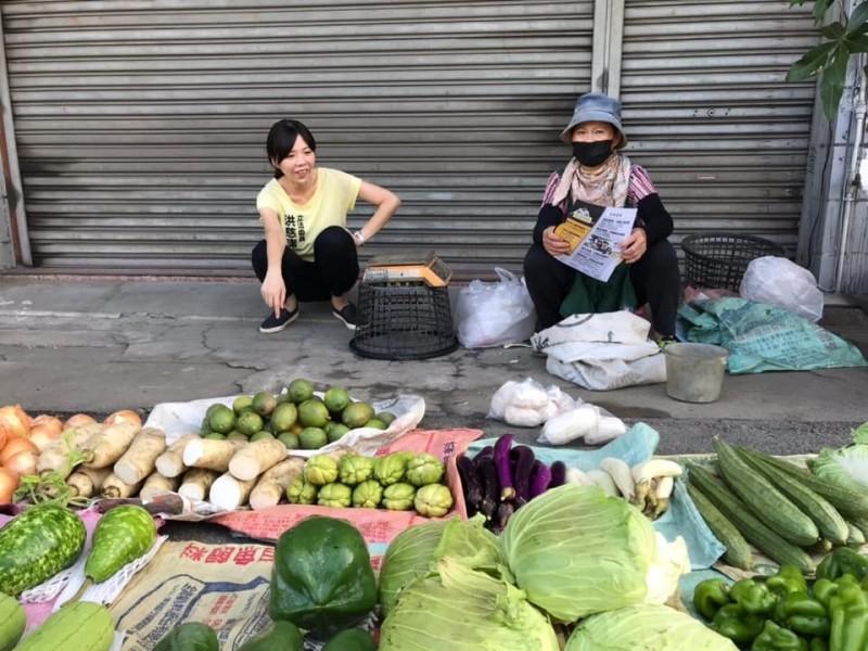 立委洪慈庸蹲著和賣菜的阿姨閒話家常,被網友稱讚「很接地氣」。(洪慈庸服務處提供)