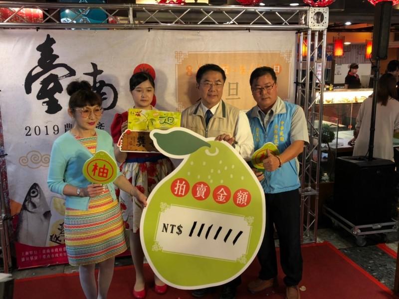 南市巡守大隊長宋俊明(右一)從市長黃偉哲(右二)拍賣手中以一一萬一一一一元標下一箱比賽得獎的文旦王。(記者王俊忠翻攝)