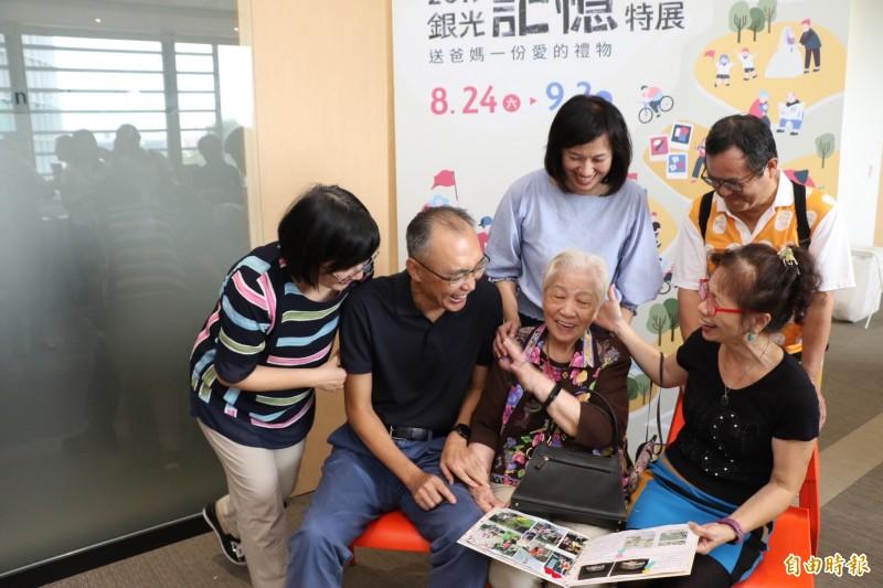 95歲的黃顧月娥(中坐者)看到媳婦葉翠媚(右前坐者)為她做的生命繪本  非常開心;左起社會局長張錦麗、副市長謝政達,以及銀光未來創新協會理事長許育寧。 (記者何玉華攝)
