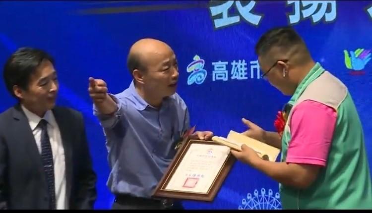 三川里長莊晉勳(右)拿出罷韓連署書,韓國瑜手指其他方向示意要他離開。(記者洪臣宏翻攝)