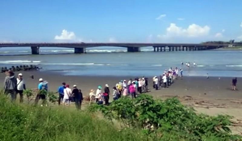 宗教團體五十多人排成人龍在鹽水溪畔違法放生螃蟹及魚類。(記者蔡文居翻攝)