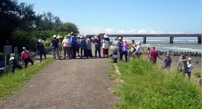 一群人排成人龍在鹽水溪畔違法放生螃蟹及魚類。(記者蔡文居翻攝)