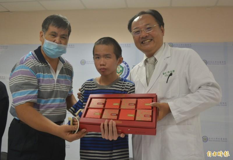 中秋節前夕,王宏至(中)今天和爸爸(左)回到醫院,送上月餅感謝救命恩人亞大醫院林志隆主任(右)。(記者陳建志攝)