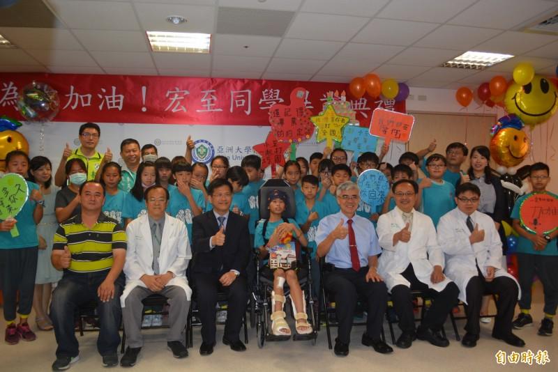 王宏至(左4)經治療,在去年6月12日出院,並在醫院舉辦畢業典禮,當時市長林佳龍(左3)和同學都出席,當時他還只能坐在輪椅上。(資料照,記者陳建志攝)