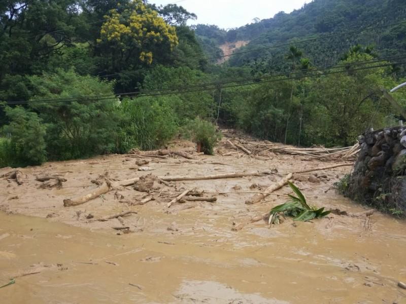 南投山區日前大雨不斷,導致位在水里鄉上安村的山坡地發生崩塌(遠方),造成土石流影響聯外道路交通。(記者劉濱銓翻攝)
