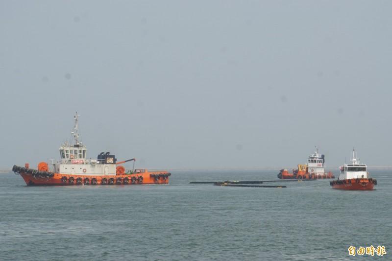 船隻利用攔油索避免漏出的污油擴大範圍。(記者詹士弘攝)
