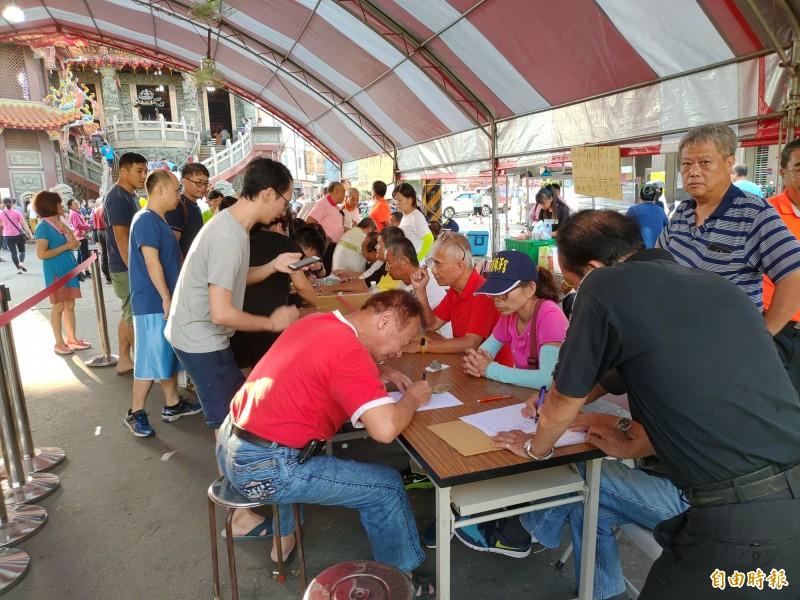 接近下午5點,仍有大批民眾在埔鹽順澤宮登記台前排隊登記索取冠軍帽。(記者陳冠備攝)