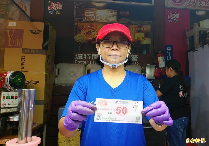 攤商收到夜市抵用券,歡迎民眾多使用。(記者張菁雅攝)