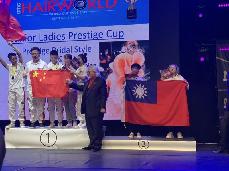 台灣代表隊獲團體組第2名,看見中國隊選手舉國旗領獎,台灣隊也不遑多讓,照樣拿出國旗同台領獎。(莊敬高職提供)