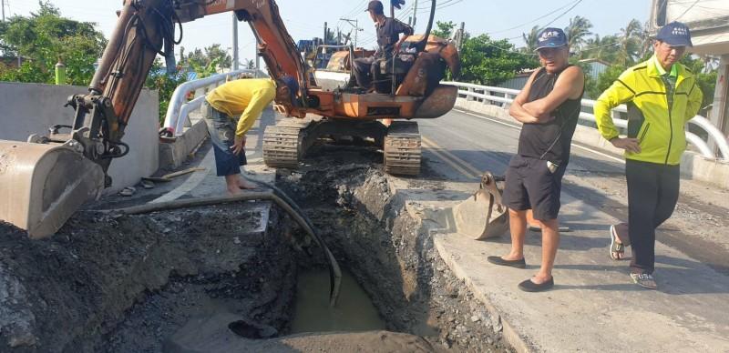 林邊「函仔口橋」自來水管破裂,水淹道路,自來水公司派員搶修。(記者陳彥廷翻攝)