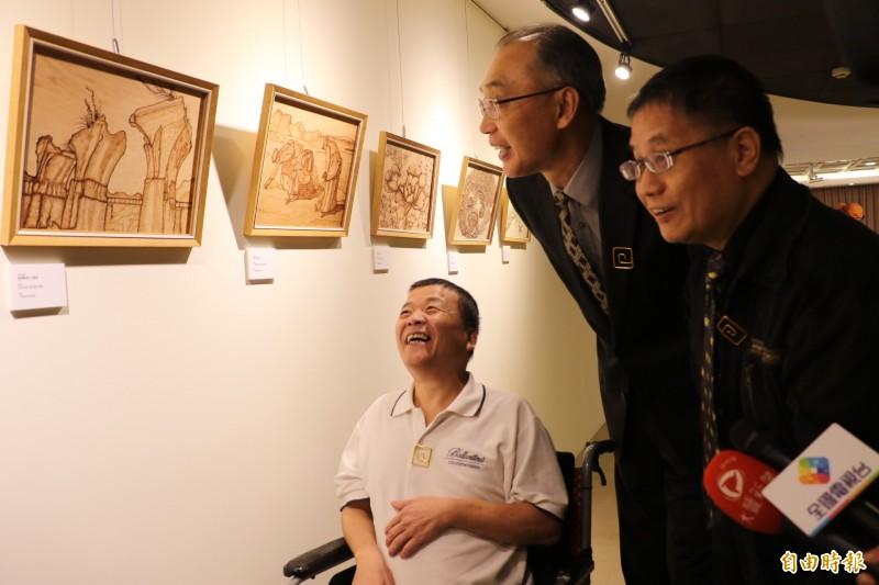 王慶順向來賓介紹他的燒烙畫創作,燒出龍騰斷橋、蘭嶼風光和拾穗等美景。(記者翁聿煌攝)