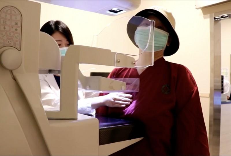 王婦示範做乳房攝影,呼籲女性應定期做乳癌篩檢。(記者蔡淑媛翻攝)